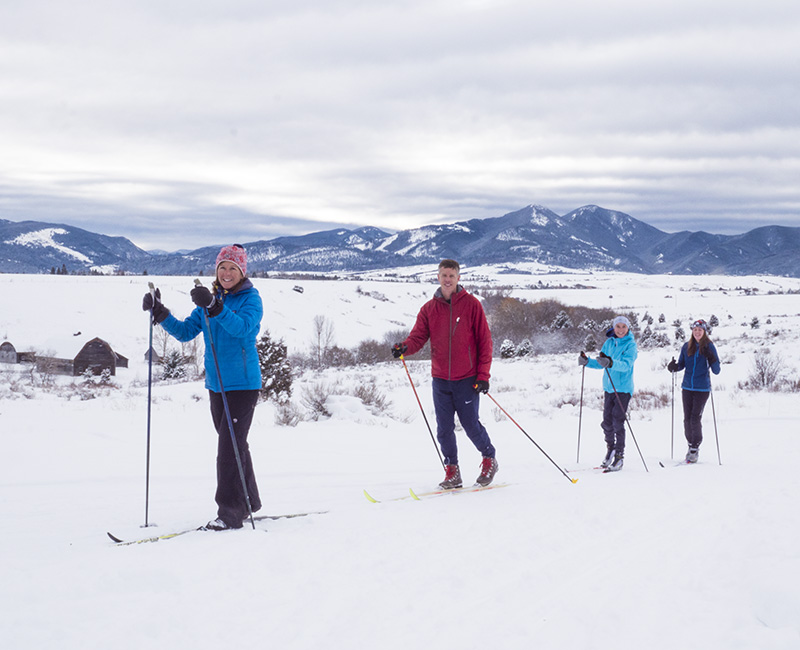 Mike McCormick cross country skiing outdoors in Bozeman, MT with his wife, two daughters, and two dogs